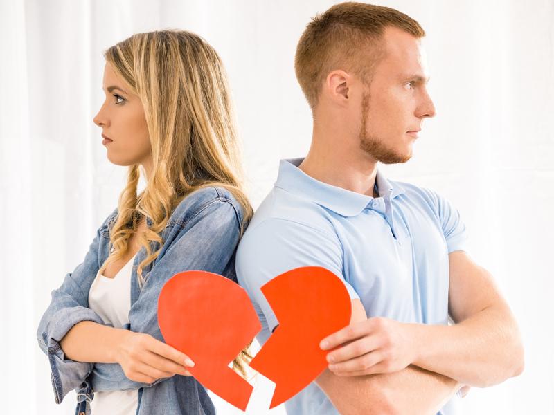 Couple, dos à dos, tenant chacun un bout de coeur rouge brisé.