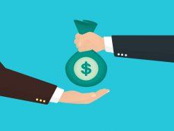 Une main tendant un sac d'argent à une autre main.