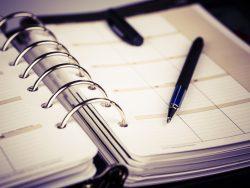 Un agenda ouvert avec un stylo posé dessus