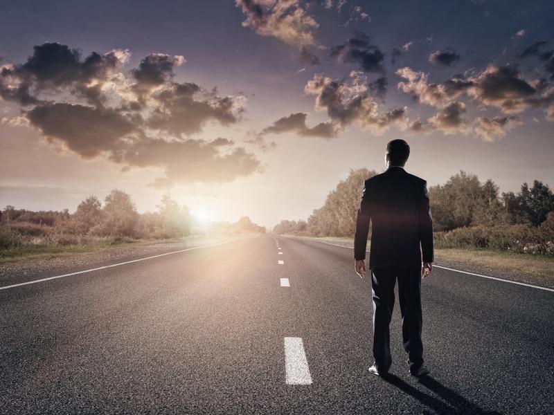 Homme d'affaires se tenant sur une route déserte, fixant l'horizon.