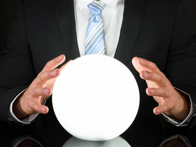 Un homme d'affaire devant une boule de cristal.