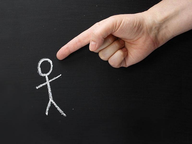 une main pointe du doigt un stickman dessiner sur un tableau noir