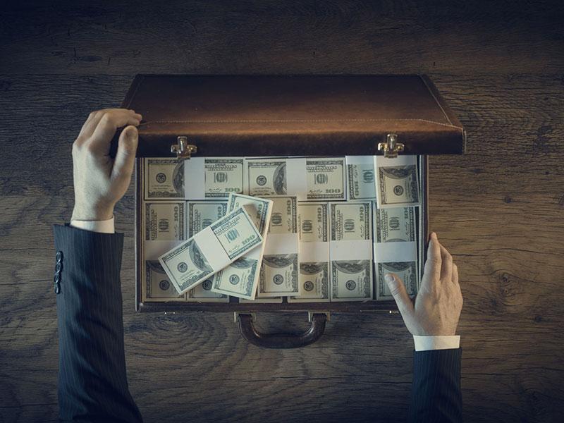 Valise ouverte remplie de billets de banque.