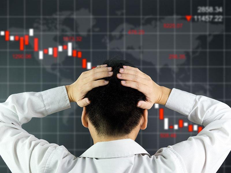 Homme d'affaire de dos, les mains sur la tête, devant un tableau montrant des indices boursiers à la baisse.