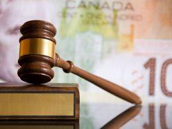 Marteau de justice posé sur un livre, un billet de banque canadien en arrière-plan