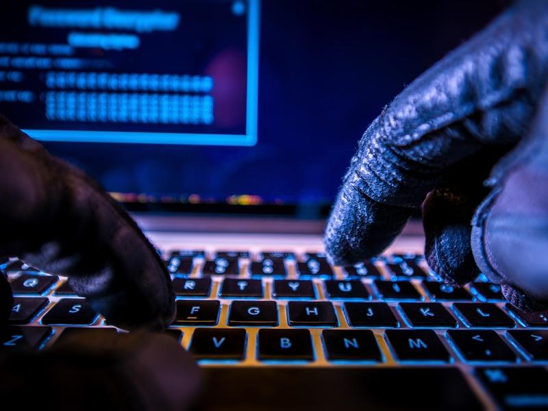 Un ordinateur sur lequel tapent deux mains gantées.