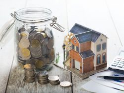 Une petite maquette de maison posée sur une table entre une calculette et un pot en verre rempli de pièce de monnaies.