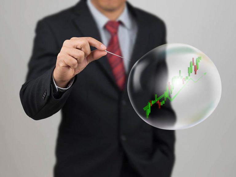 Homme d'affaire s'apprêtant à faire éclater une bulle avec une aiguille.