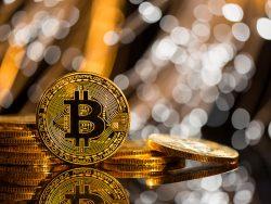 Un bitcoin posé debout vers un tas d'autres bitcoins.