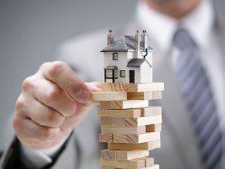 Un homme d'affaire enlevant un plot d'une tour en bois où est posé une petite maison dessus