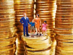 Une famille de petits personnages posée sur un tas de pièces.