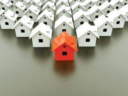 Une maison rouge entourée de plusieurs maisons blanches.