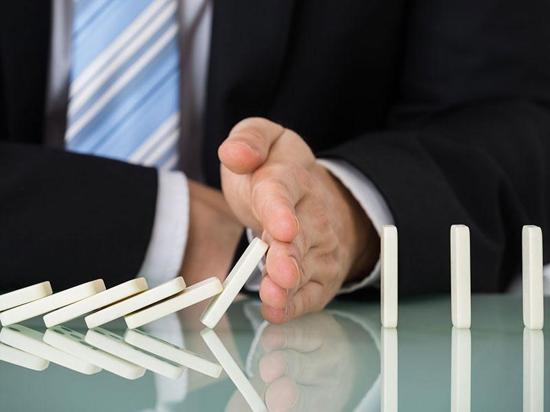 Homme d'affaire arrêtant une chute de dominos.