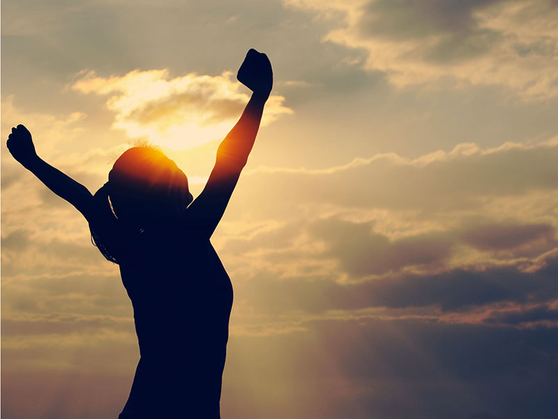 Femme bras ouverts devant un coucher de soleil.
