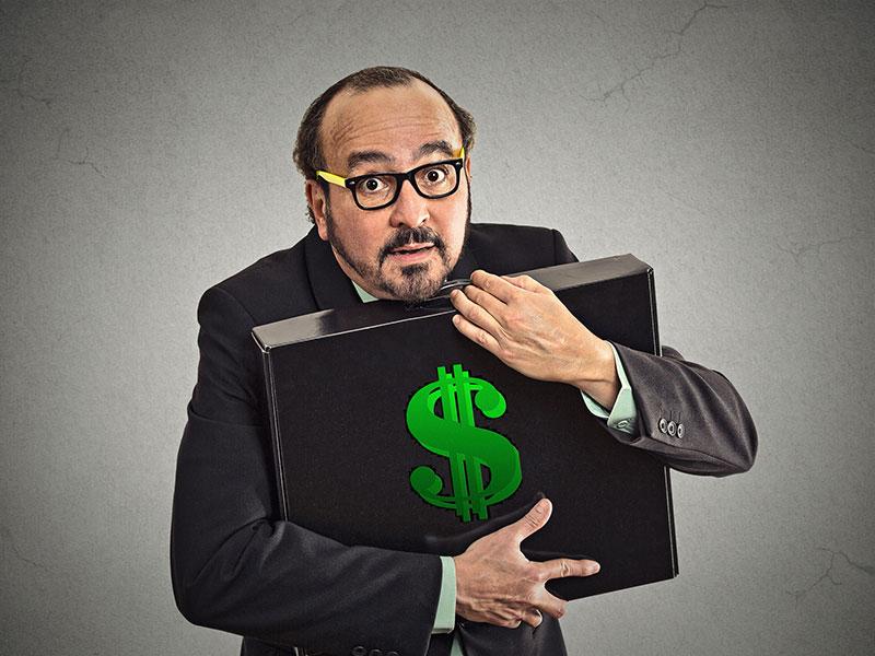 Homme d'affaire tenant une valise contenant de l'argent.