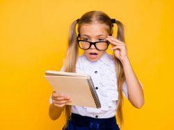 Fillette portant des lunettes noires, surprise en lisant un document.