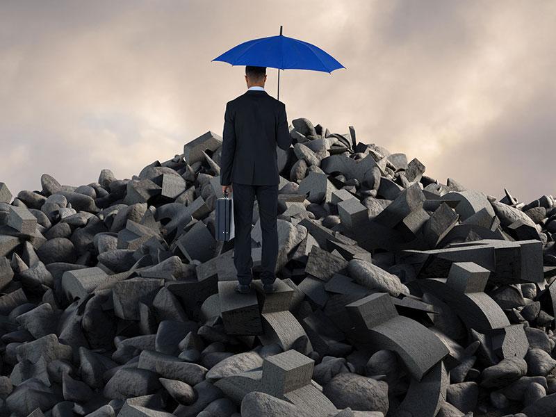 Homme d'affaires debout sur un tas de pierres.