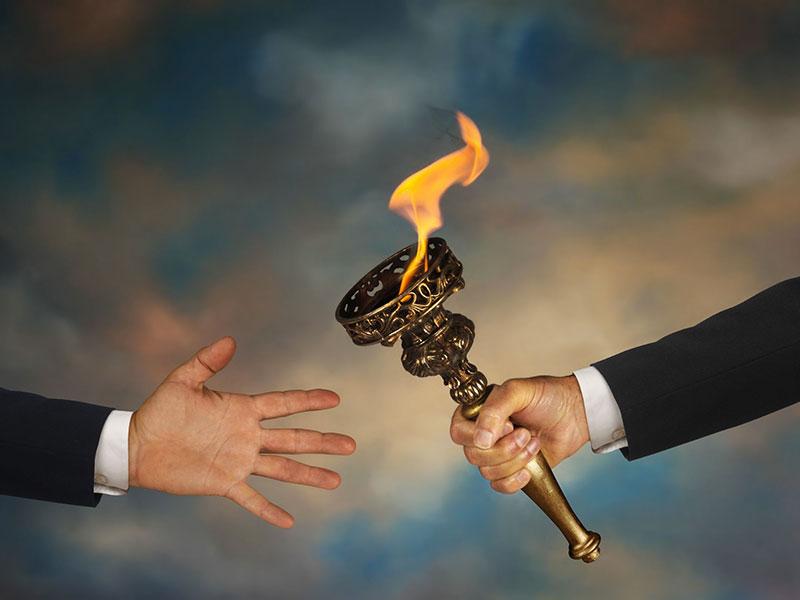 Un flambeau est passé d'une main à une autre.