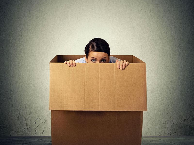 Femme qui a peur et qui se cache dans une boîte de carton.
