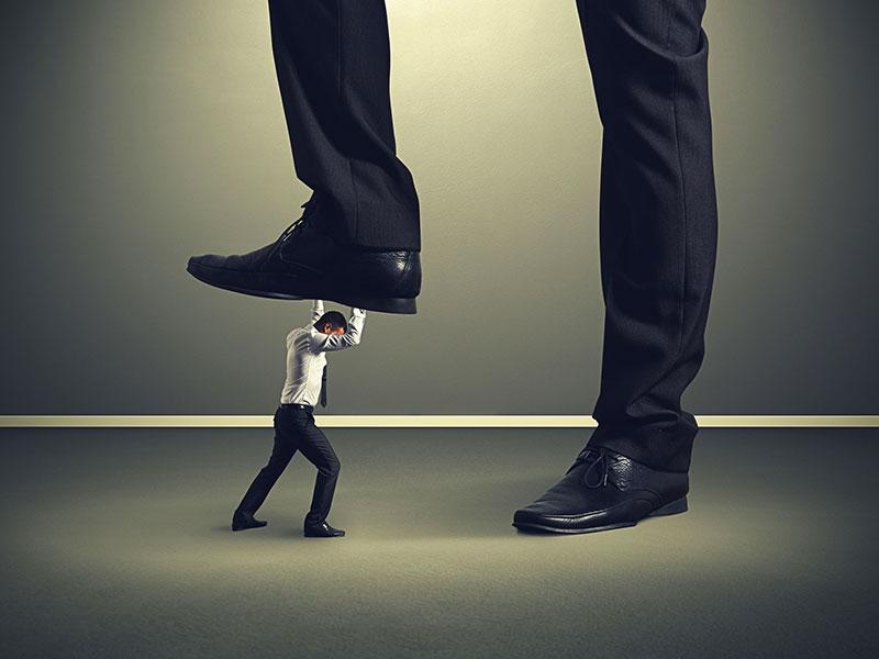 Homme miniature résistant au pied d'un géant qui tente de l'écraser.