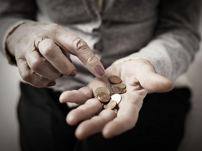 Personne âgée comptant des pièces de monnaie qu'elle tient dans sa main.