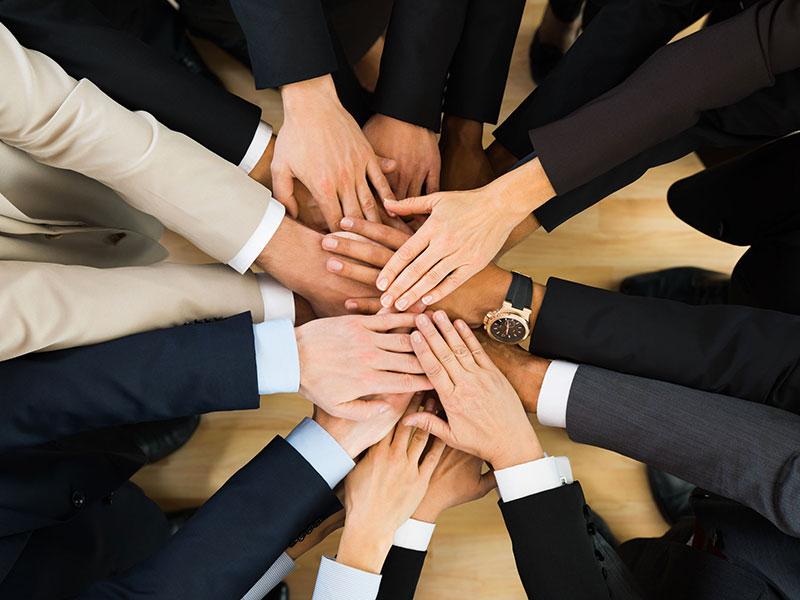 Hommes d'affaires les mains réunies.