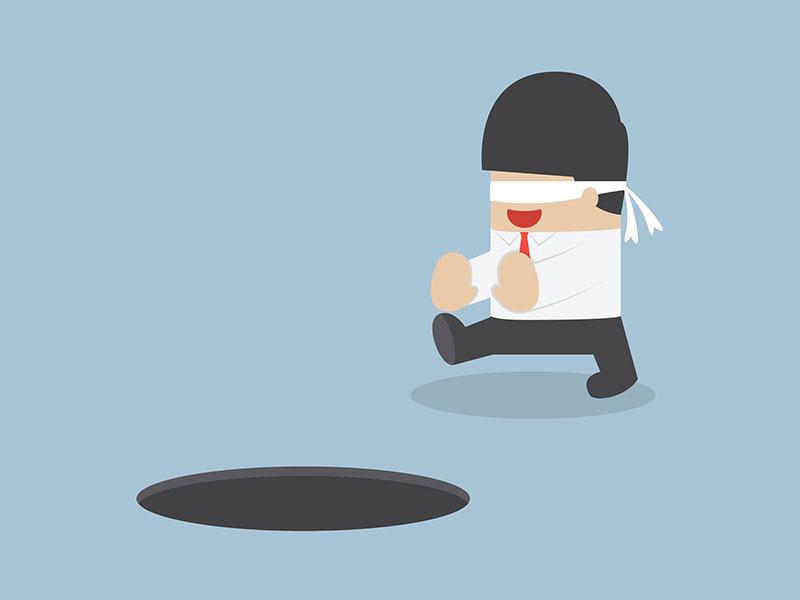 Personnage aux yeux bandés s'apprête à tomber dans un trou dans le sol.
