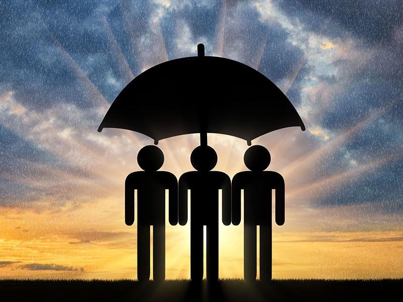 Trois personnes à l'abri sous un parapluie, devant un coucher de soleil.