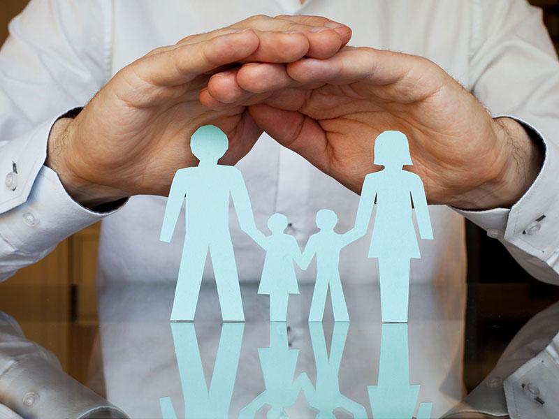 Conseiller posant ses mains au-dessus d'une famille en papier.