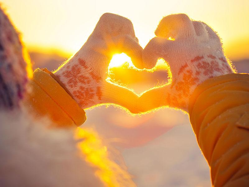 Coeur formé avec les mains, avec coucher du soleil en arrière-plan.