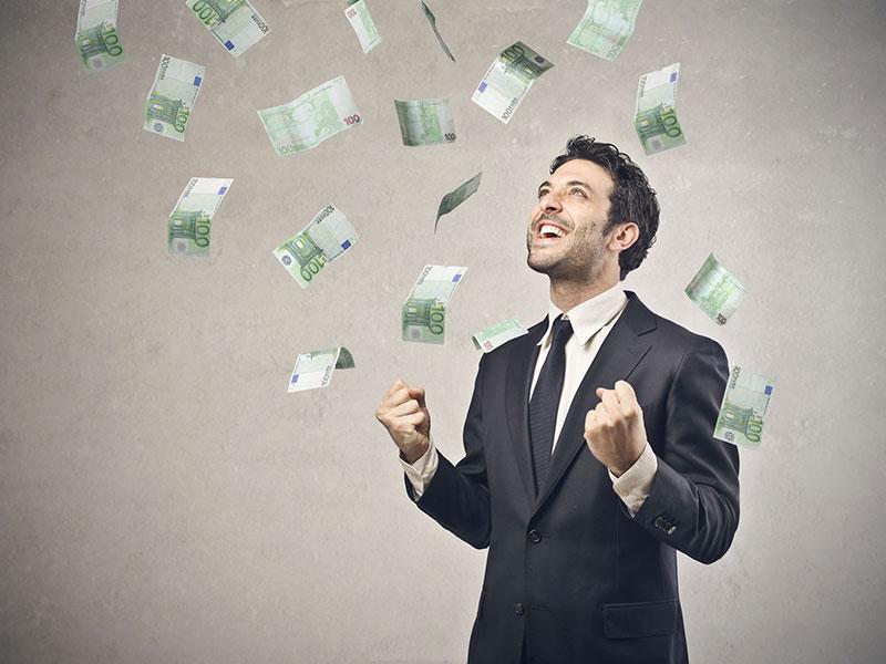 Homme d'affaires heureux sur qui tombe une pluie de billets de banque.