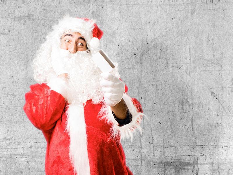 Père Noel tenant une carte de crédit.