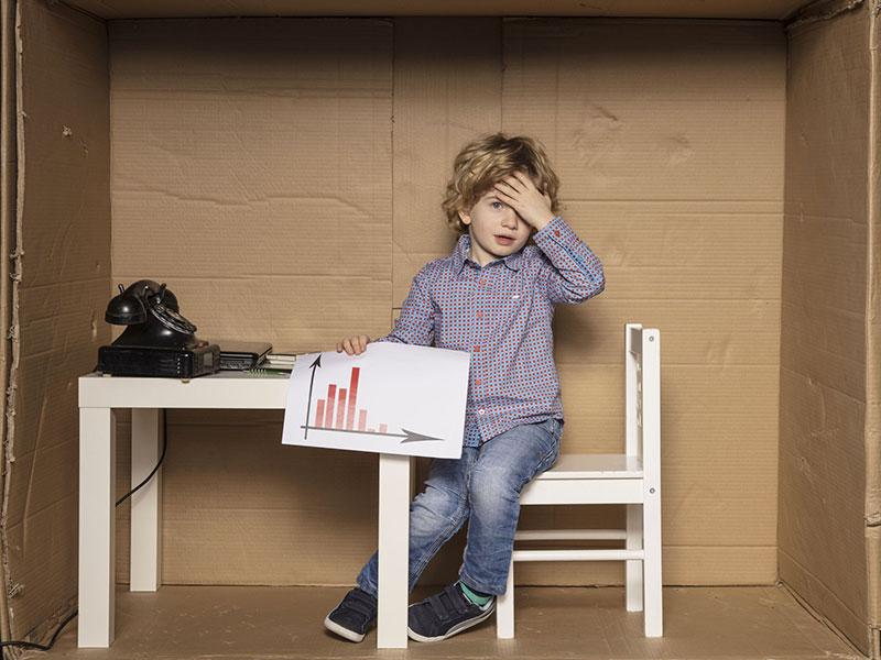 Enfant l'air découragé, tenant une feuille contenant un graphique économique.