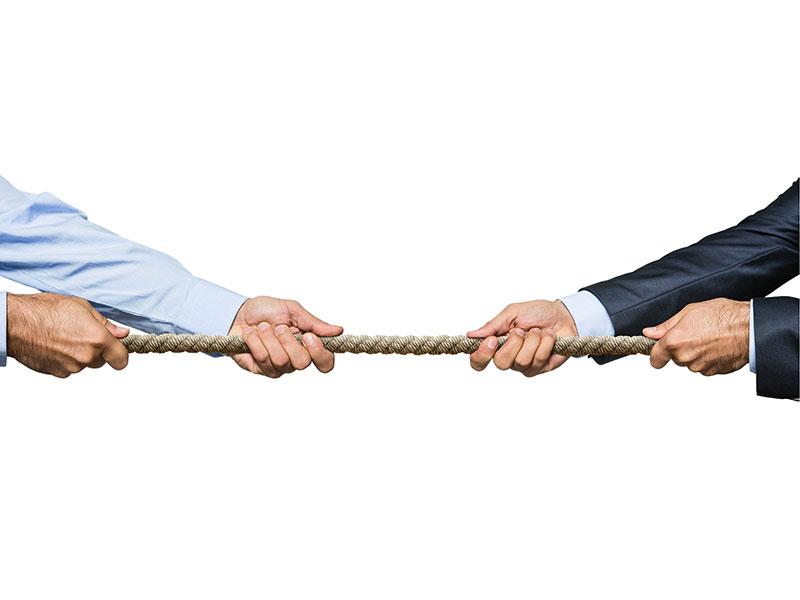 Deux hommes d'affaires en train de tirer une corde pour mesurer leur force.