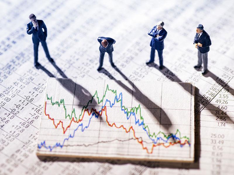 Concept d'investisseurs observant, inquiets, les courbes d'un tableau boursier.