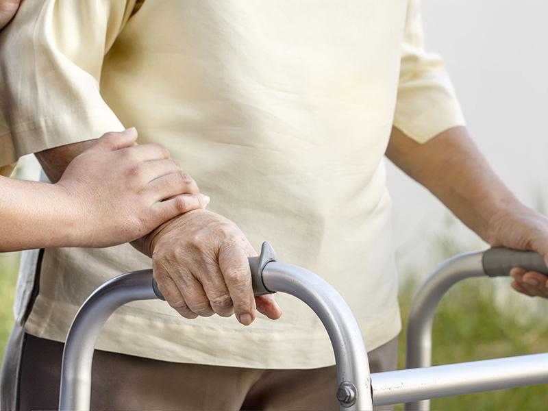 Personne âgée marchant avec un déambulateur.