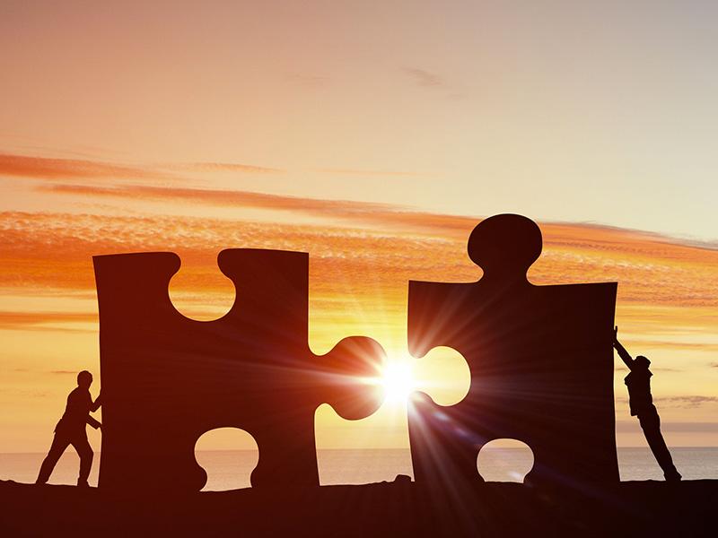 Deux personnes poussent chacune une immense pièce de puzzle afin de les imbriquer.