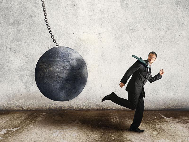 Homme d'affaires pourchassé par une boule de démotion.