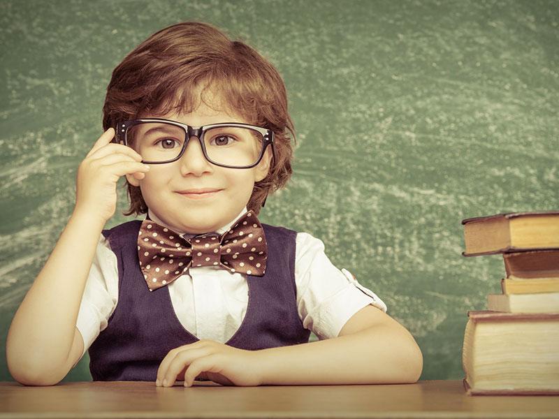 Jeune garçon assis au pupitre du professeur.