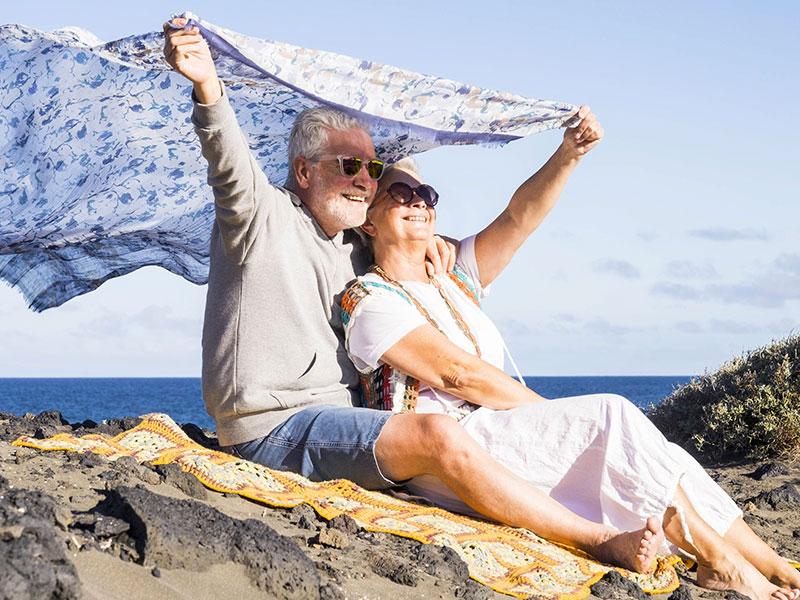 Couple de retraités assis sur un rocher près de la mer.