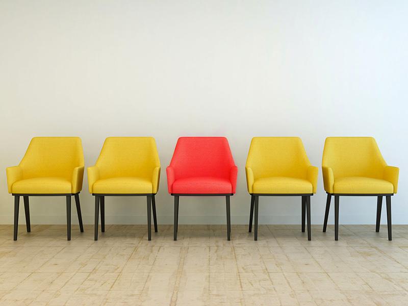 Chaises alignées de la même couleur, sauf une de couleur différentes.
