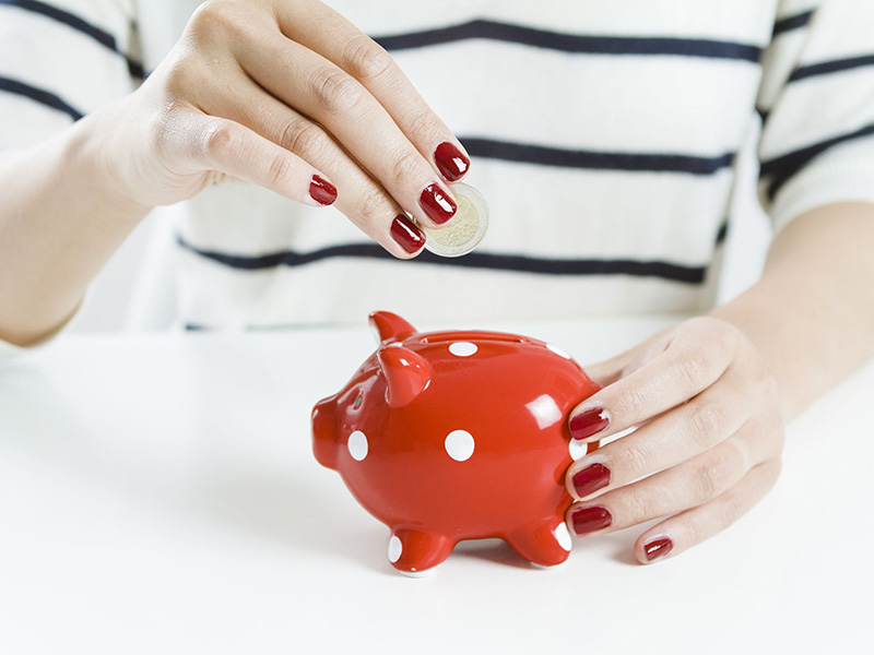 Femme déposant une pièce de monnaie dans une tirelire rouge.