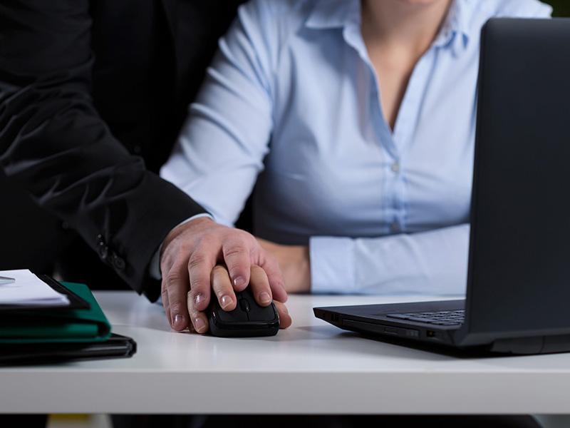 Homme plaçant sa main sur celle d'une femme en train de travailler.