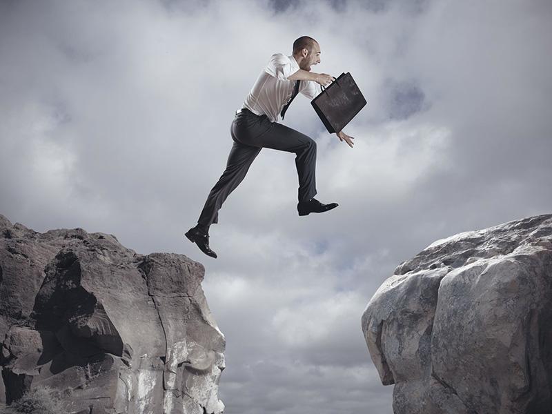 Homme d'affaires sautant par-dessus un précipice.