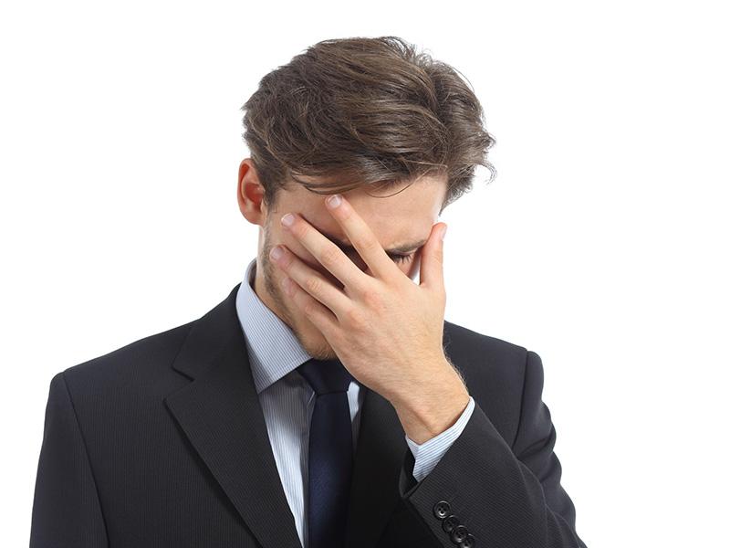 Homme d'affaires se cachant le visage avec la main.
