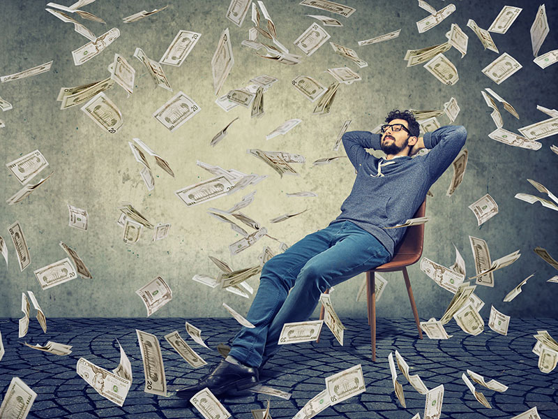 Jeune homme assis sur une chaise alors que tombe autour de lui une pluie de billets de banque.