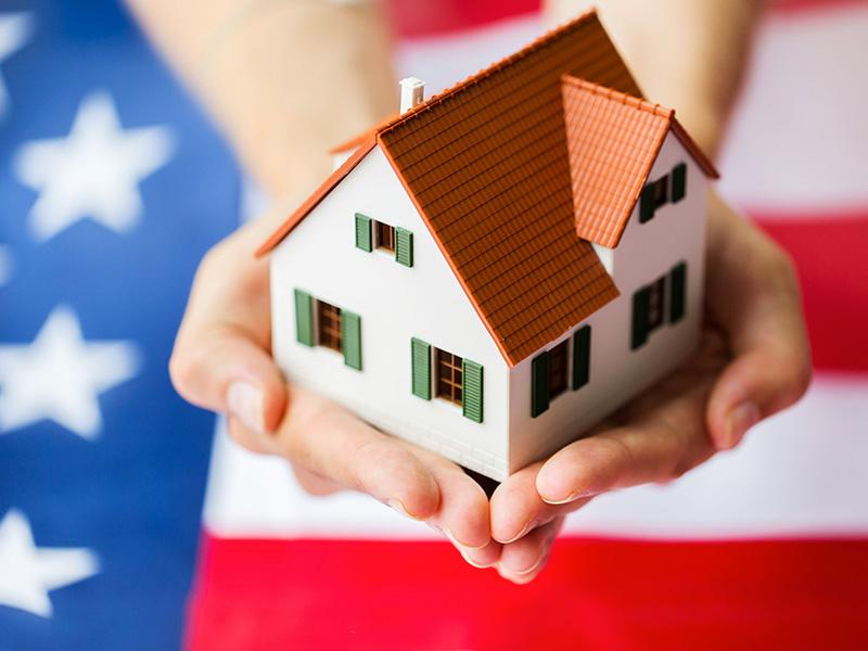 Petite maison tenue dans les mains d'une jeune femme, avec drapeau américain en arrière-plan.