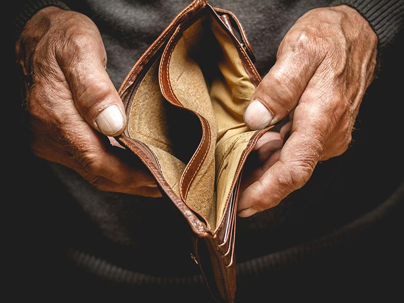 Portefeuille vide tenu par une personne âgée.