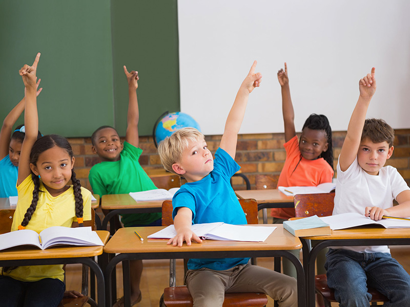 Enfants dans une salle de classe, la main levée.