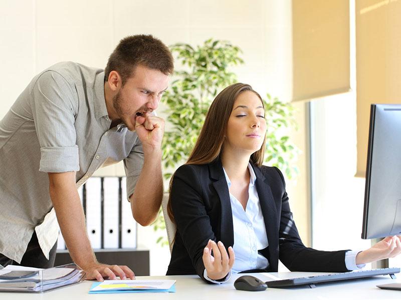 Femme d'affaires zen devant un écran d'ordinateur, un homme anxieux derrière elle.
